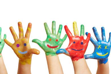 Panorama aus vielen bunten Kinderhänden mit aufgemalten Smileys